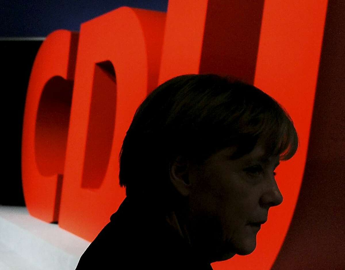 German Chancellor Angela Merkel walks in front of a CDU-Party sign of the German Christian Democrats Party (CDU) convention in Leipzig, Germany, Monday, Nov. 14, 2011. (AP Photo/Jens Meyer) Ran on: 11-15-2011 German Chancellor Angela Merkel walks in front of a sign for her party, the Christian Democratic Union, at a conference in Leipzig, Germany. Ran on: 11-15-2011 German Chancellor Angela Merkel walks in front of a sign for her party, the Christian Democratic Union, at a conference in Leipzig, Germany.