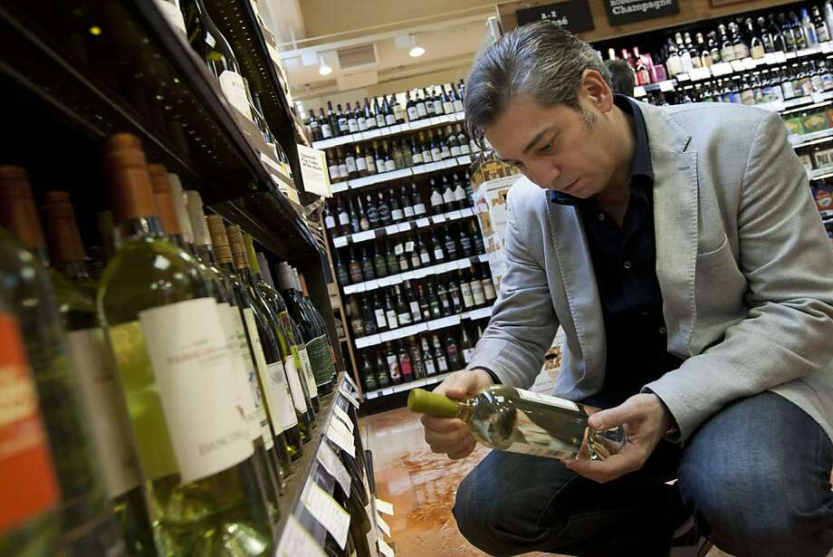 Nicolas Luisotti, San Francisco Opera director, looks for a bottle of white wine to cook with while he grocery shops with his wife, Rita Simonini, at the Whole Foods Market on Franklin Street in San Francisco, CA Thursday morning, October 20, 2011. Photo by Erin Lubin/Special to Chronicle Photo: Erin Lubin, Special To The Chronicle