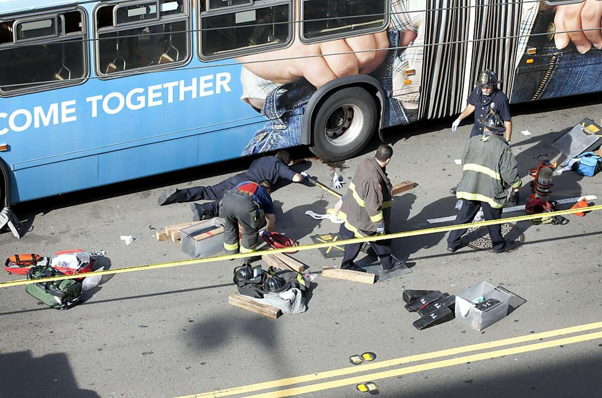 Emergency workers inspect the scene of a Muni accident that resulted in the death of a pedestrian on Mission St. between 5th and 6th Streets on Sunday, November 13, 2011, in San Francisco, Calif.