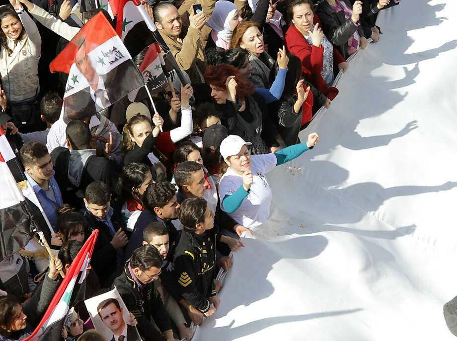 Their shadows reflected on the white of their national flag, Syrian's rally to show their support for their President Bashar al-Assad in the capital in Damascus on November 13, 2011, a day after the Arab League suspends Syria until President Bashar al-Assad implements an Arab deal to end violence against protesters, calling for sanctions and transition talks with the opposition.  AFP PHOTO/LOUAI BESHARA (Photo credit should read LOUAI BESHARA/AFP/Getty Images) Photo: Louai Beshara, AFP/Getty Images