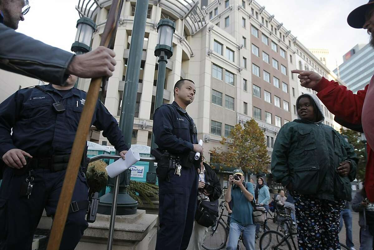 OPD officer H. Nguyen (center) is surrounded by protestors as they give out notices of violation to those camping at the Occupy Oakland, at Frank Ogawa Plaza in downtown Oakland, Calif., on Sunday, Nov. 13, 2011.