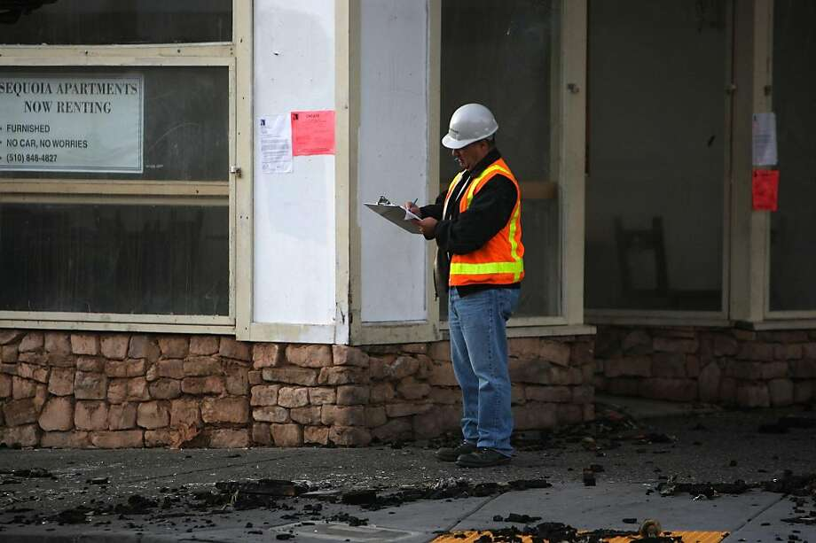 A construction worker taking notes at the apartment building on Haste St. at Telegraph Ave., which was home to Cafe Intermezzo, Raleigh's Bar and Grill, and Thai Noodle II on the ground level, which had burned over the weekend near UC Berkeley in Berkeley, Calif. starting late Friday evening.  Structurally unsafe, the immediate area is closed to the public on Monday, November 21, 2011. Photo: Liz Hafalia, The Chronicle