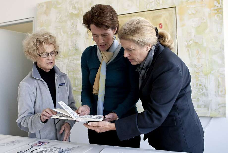 Artist Carla Saunders shows Dr. Jennifer Brokaw and registered nurse Sara Stephens (left to right) a book of drawings she made while she was undergoing radiation treatment for a tumor in San Francisco, Calif., on Thursday, November 17, 2011.  Saunders was one of Stephens and Brokaw's patients at Good Medicine, a patient advocacy service they started in San Francisco. Photo: Laura Morton, Special To The Chronicle