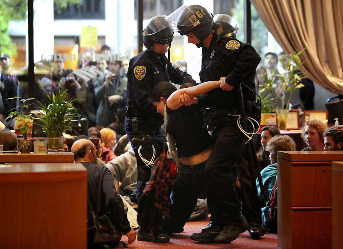 A protesters is carried out of the bank after refusing to stand as she is arrested inside the Bank of America in the financial district, Wednesday November 16, 2011 in San Francisco, Calif. The arrests happened after a march of hundreds of students march through the streets of San Francisco.