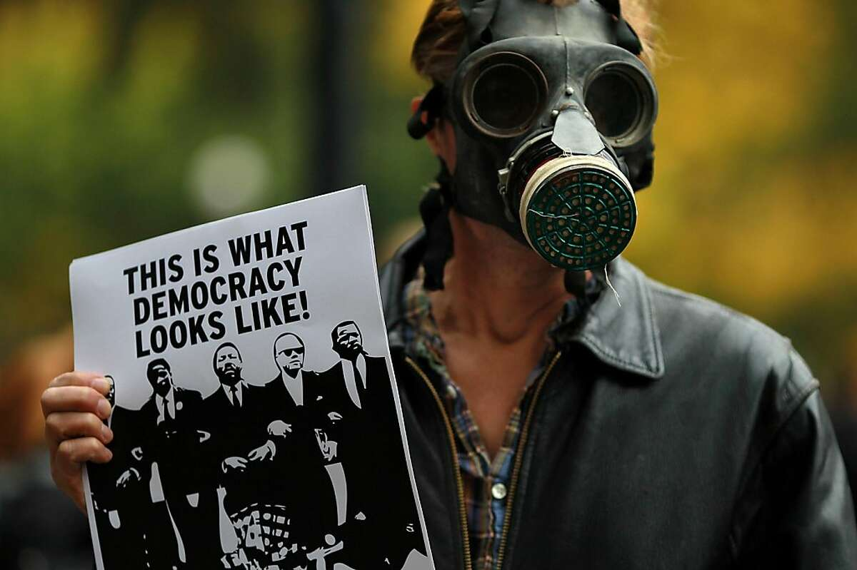 DAVIS, CA - NOVEMBER 21: An Occupy protestor wears a gas mask during a demonstration at the UC Davis campus on November 21, 2011 in Davis, California. Thousands of Occupy protestors staged a demonstration on the UC Davis campus to protest the UC Davis police who pepper sprayed students who sat passively with their arms locked during an Occupy Wall Street demonstration on November 18. (Photo by Justin Sullivan/Getty Images)