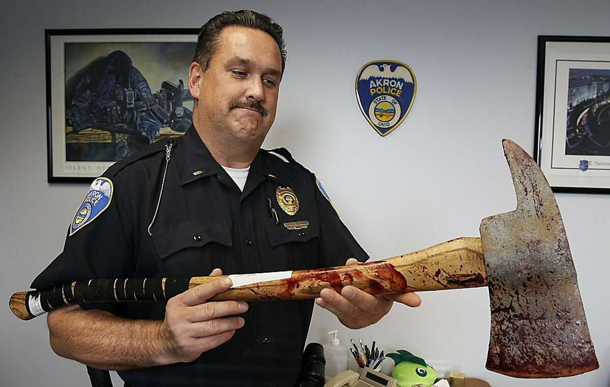 In a Thursday Nov. 17, 2011 photo, Akron Police Lt. Rick Edwards holds a very realistic rubber ax confiscated from Bill Morrison. Morrison was arrested on Oct. 16 for inducing panic and jailed overnight after he tried to sell the ax at a local Akron bar. (AP Photo/Akron Beacon Journal, Paul Tople) MANDATORY CREDIT
