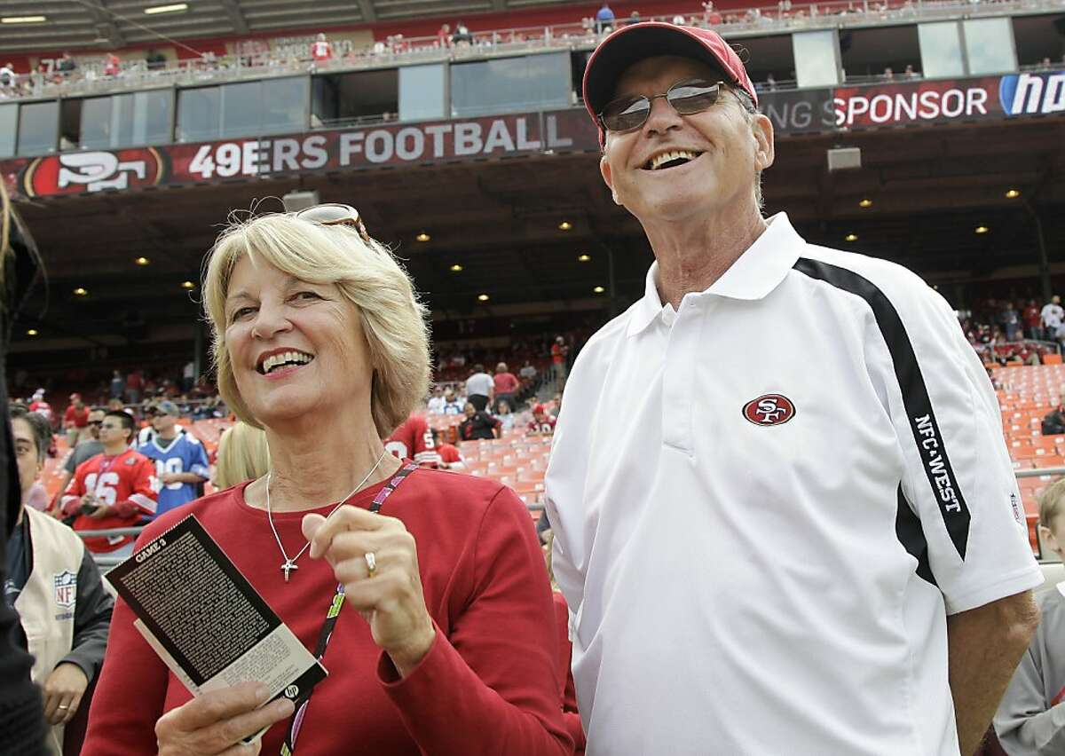 FILE - In this Sept. 11, 2011 file photo, Jackie and Jack Harbaugh, parents of San Francisco 49ers coach Jim Harbaugh, and Baltimore Ravens coach John Harbaugh, stand before an NFL football game between the 49ers and the Seattle Seahawks, in San Francisco. Jack Harbaugh has watched his sons go at it for nearly five decades. That's why he sees no need to be there in person for Thursday's, Nov. 24, 2011 history-making matchup between his sons. (AP Photo/Paul Sakuma, File)