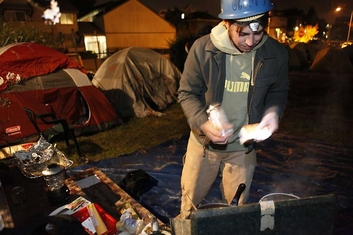 Aaron Thomas of Oakland prepares some food for Occupy Oakland campers at a new camp at 18th and Linden Streets. A small group of about 30 Occupy Oakland protesters set up camp at a vacant lot at the corner of 18th and Linden Streets in Oakland, Calif., on Monday night, November 21, 2011. They expect more to join them.