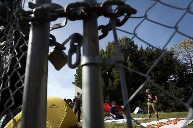 A new Occupy Oakland encampment has sprung up in the yard of a foreclosed home in Oakland, Calif., Tuesday, November 22, 2011.  Earlier Tuesday members of the camp were seen trying to forcibly remove this lock on the gate leading into the property. Photo: Sarah Rice, Special To The Chronicle