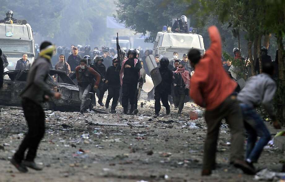 Protesters throw stones during clashes with the Egyptian riot police near Tahrir square in Cairo, Egypt, Tuesday, Nov.  22, 2011. Egypt's civilian Cabinet has offered to resign after three days of violent clashes in many cities between demonstrators and security forces, but the action failed to satisfy protesters deeply frustrated with the new military rulers. (AP Photo/Khalil Hamra) Photo: Khalil Hamra, AP