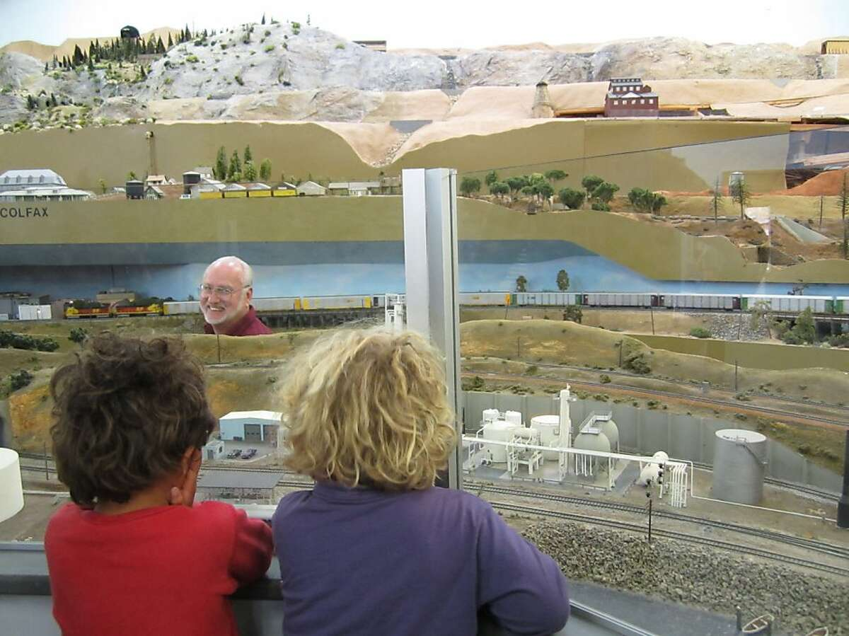 Randy Smith, (white hair) General Manager of the GSRMR, watches kids enjoy the displays at the museum. Ran on: 11-24-2011 General manager Randy Smith (facing forward) watches children enjoy the displays at the Golden State Model Railroad Museum.