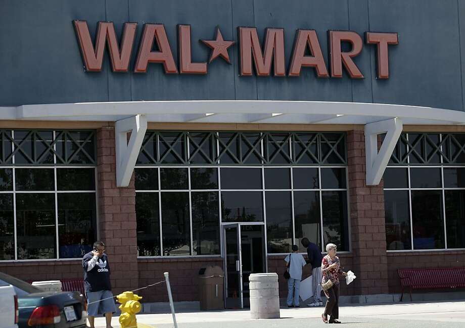 People pass in front of a Wal-Mart store in San Diego, Monday, May 3, 2010. Wal-Mart Stores Inc. has agreed to pay $27.6 million to settle allegations that it improperly handled and dumped hazardous waste at stores across California, prosecutors said Monday. (AP Photo/Gregory Bull)  Ran on: 05-16-2010 Walmart stores will start to carry Apple iPads this year.  Ran on: 10-30-2010 Walmart is using discounts to entice shoppers to spend. Consumer confidence weakened in the third quarter. Photo: Gregory Bull, Associated Press