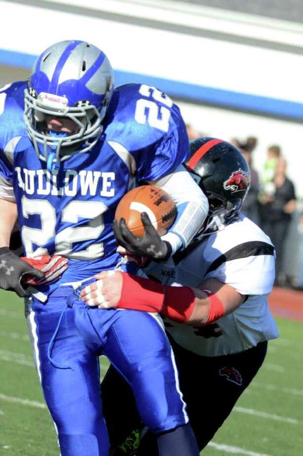 Fairfield Ludlowe's Stephen Scholz is brought down by Fairfield Warde's Joe Marx during the Thanksgiving day football game at Fairfield Ludlowe High School on Thursday, Nov. 24, 2011. Photo: Amy Mortensen / Connecticut Post Freelance