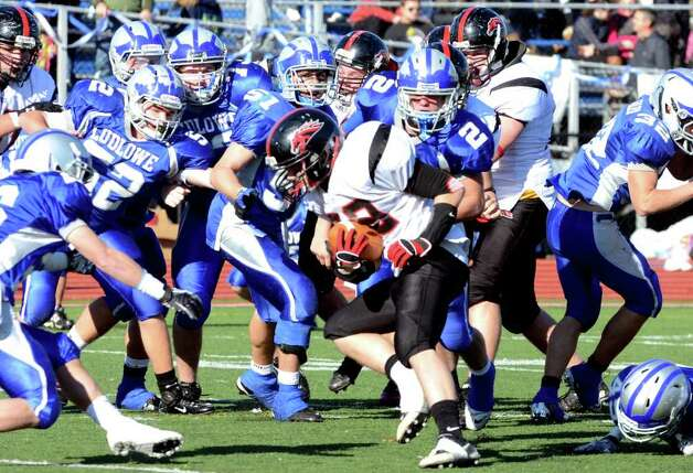 Fairfield Warde's Joseph Muratori (32) is swarmed by Fairfield Ludlowe's defense during the Thanksgiving day football game at Fairfield Ludlowe High School on Thursday, Nov. 24, 2011. Photo: Amy Mortensen / Connecticut Post Freelance