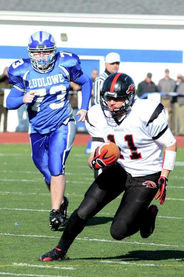Fairfield Warde's Michael Schweizer (11) carries the ball for yardage as Fairfield Ludlowe's Michael Aidan Crocker (73) follows in pursuit during the Thanksgiving day football game at Fairfield Ludlowe High School on Thursday, Nov. 24, 2011. Photo: Amy Mortensen / Connecticut Post Freelance