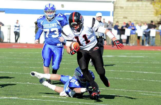 Fairfield Warde's Michael Schweizer (11) avoids a tackle by Fairfield Ludlowe's Salvatore Loris (26) during the Thanksgiving day football game at Fairfield Ludlowe High School on Thursday, Nov. 24, 2011. Photo: Amy Mortensen / Connecticut Post Freelance