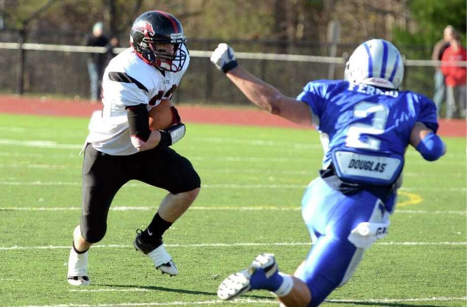 Fairfield Warde's Joseph Muratori (32) carries the ball for yardage as Fairfield Ludlowe's Patrick Ferrio (2) defends during the Thanksgiving day football game at Fairfield Ludlowe High School on Thursday, Nov. 24, 2011. Photo: Amy Mortensen / Connecticut Post Freelance