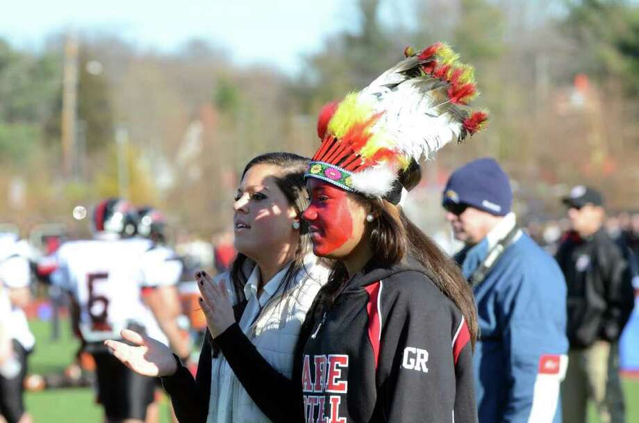 Fairfield Warde students senior Amanda Leiterman and junior Jasmine Howell, wearing a feather headdress, watch from the sidelines during the Thanksgiving day football game against cross town rival Fairfield Ludlowe at Fairfield Ludlowe High School on Thursday, Nov. 24, 2011. Photo: Amy Mortensen / Connecticut Post Freelance
