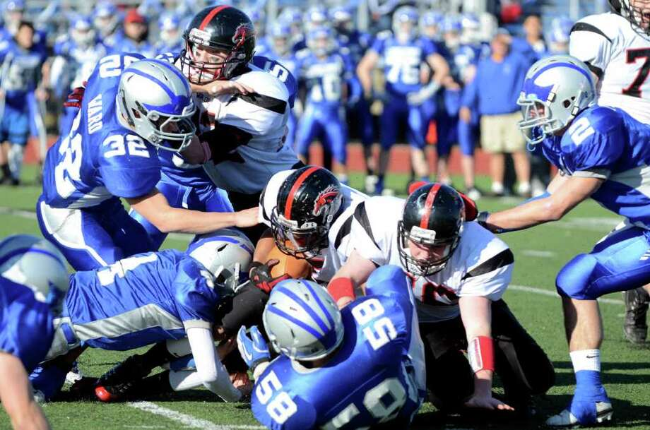 Fairfield Warde ball carrier Devin Lofton, center, is brought down by Fairfield Ludlowe's defense during the Thanksgiving day football game at Fairfield Ludlowe High School on Thursday, Nov. 24, 2011. Photo: Amy Mortensen / Connecticut Post Freelance
