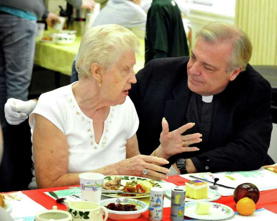 Marolyn Beschle, 87, talks with Father Joseph Krasinski during the Annual Thanksgiving Dinner at St. James Episcopal Church in Danbury, Thursday, Nov. 24, 2011. Beschle has been comming to the church since she was 4 years old. Photo: Mike Duffy, Michael Duffy / The News-Times