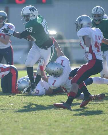 New Milford's Kih Best gets pulled down by New Fairfield's Ben Kimmel during their SWC football game Thursday, Nov. 24, 2011, at New Milford High School. Photo: Barry Horn / The News-Times Freelance