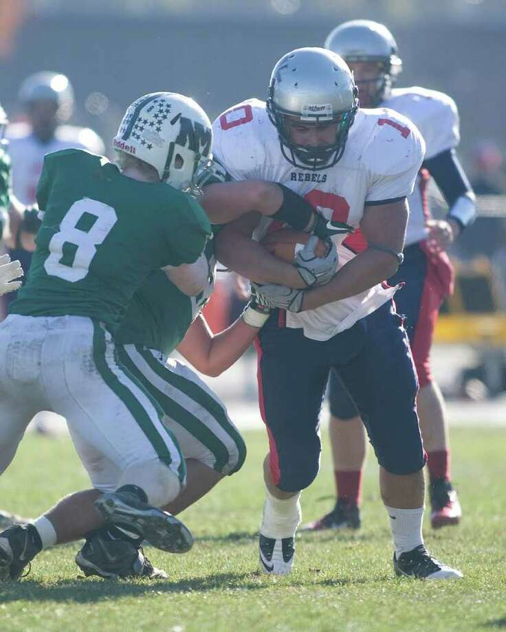New Milford linebacker Kevin VanCoughnett tries to wrestle the ball away from New Fairfield's Nick Guardi as Jesse Calhoun (8) also moves in during their SWC football game Thursday, Nov. 24, 2011, at New Milford High School. Photo: Barry Horn / The News-Times Freelance
