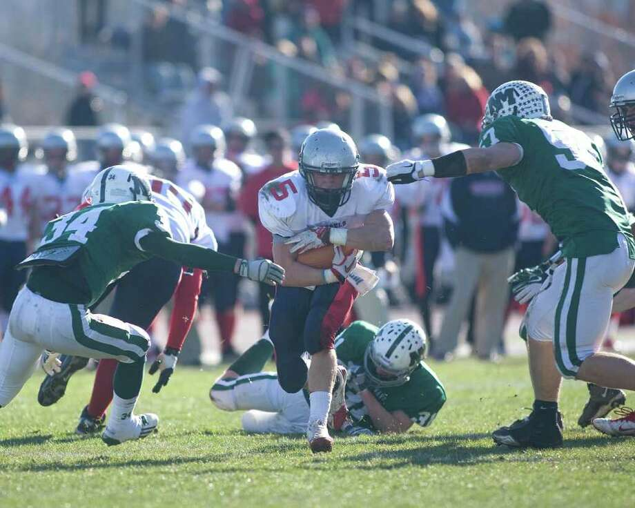 New Fairfield's Robbie Fiamengo hits the hole as New Milford's Tevan Leonard (34) and Austin Kisling close in during their SWC football game Thursday, Nov. 24, 2011, at New Milford High School. Photo: Barry Horn / The News-Times Freelance