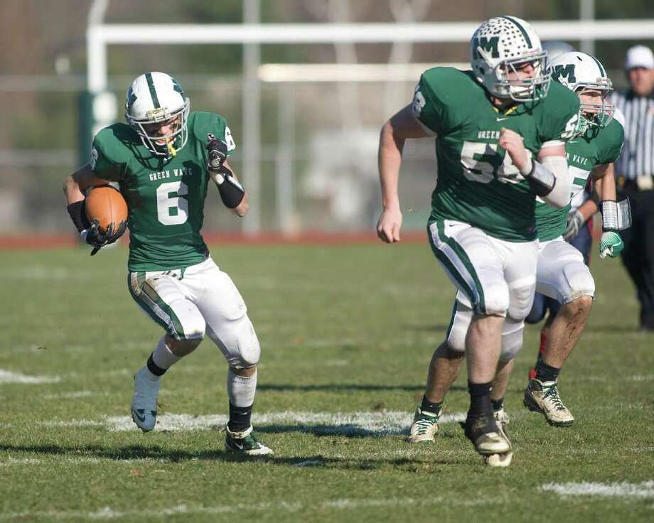 With New Milford's Blaze Martin leading the way, Kam Bradshaw (6) gains yardage against New Fairfield during their SWC football game Thursday, Nov. 24, 2011, at New Milford High School. Photo: Barry Horn / The News-Times Freelance