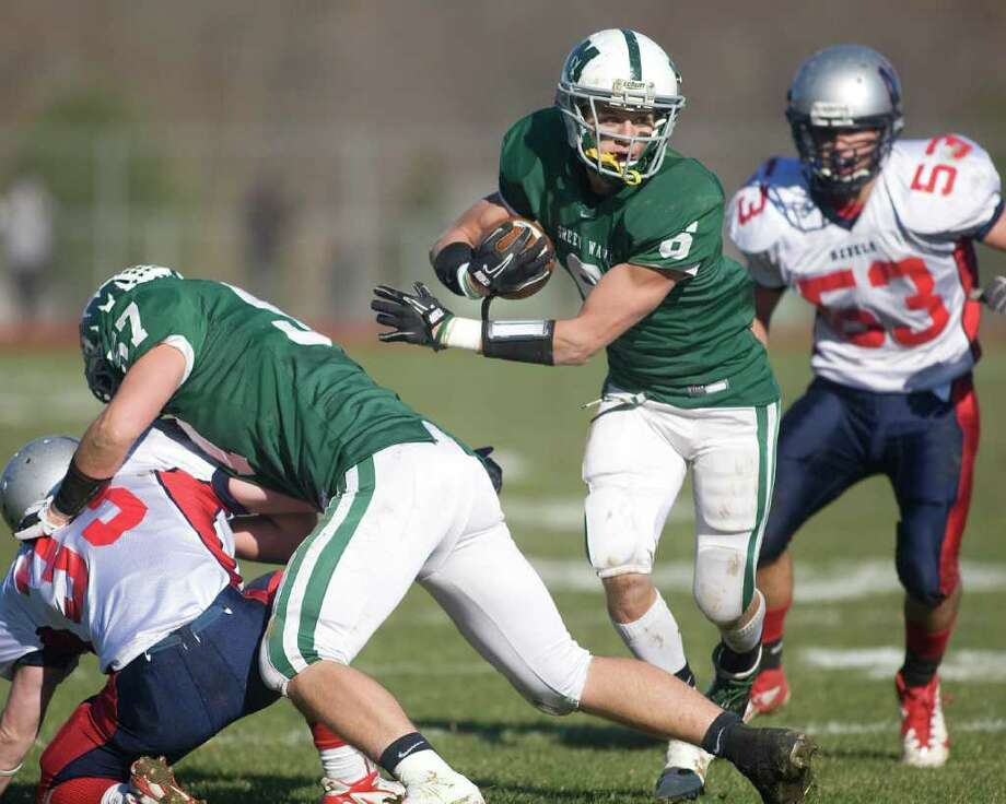 New Milford's Austin Kisling (57) provides the key block on New Fairfield's James Colella to spring Kam Bradshaw loose during their SWC football game Thursday, Nov. 24, 2011, at New Milford High School. Photo: Barry Horn / The News-Times Freelance