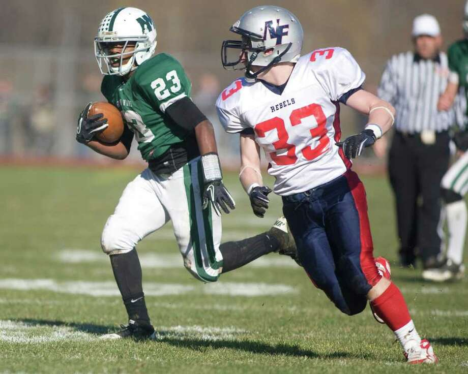 New Milford's Kih Best gets around New Fairfield 's James Colella en route to a touchdown run during their SWC football game Thursday, Nov. 24, 2011, at New Milford High School. Photo: Barry Horn / The News-Times Freelance