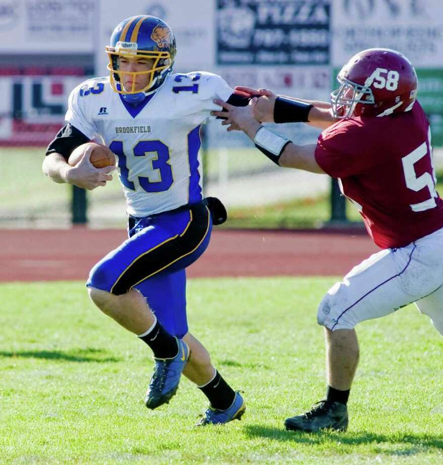 Brookfield High School quarterback tries to escape Bethel High School's Tyler Gall during a football game at Bethel. Thursday, Nov. 24, 2011 Photo: Scott Mullin / The News-Times Freelance