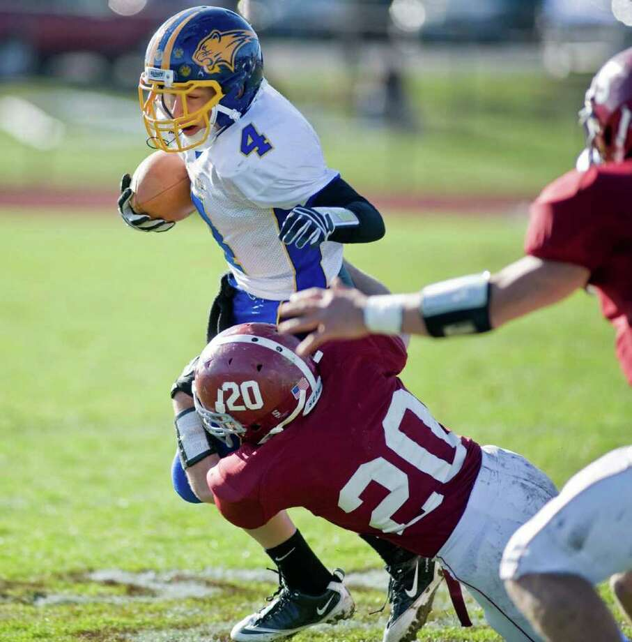 Brookfield High School's Brad Westmark is pulled down by Bethel High School's William Quinn during a football game at Bethel. Thursday, Nov. 24, 2011 Photo: Scott Mullin / The News-Times Freelance