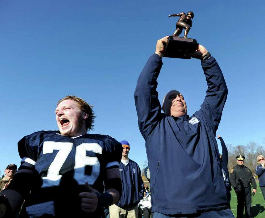 Jack Gibson # 76 of Staples High School shouts out as his coach Marce Petroccio holds the McDougall Trophy over his head at the conclusion of the FCIAC Football Championship game in which Staples High School defeated Greenwich High School 31-27 at Staples, Westport, Thursday afternoon, Nov. 24, 2011. Photo: Bob Luckey / Greenwich Time