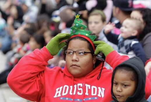Kayla Cooper adjusts her Christmas tree headband as she and daughter, Kimora Campbell, 5, watch the parade. Photo: Melissa Phillip, Houston Chronicle / © 2011 Houston Chronicle