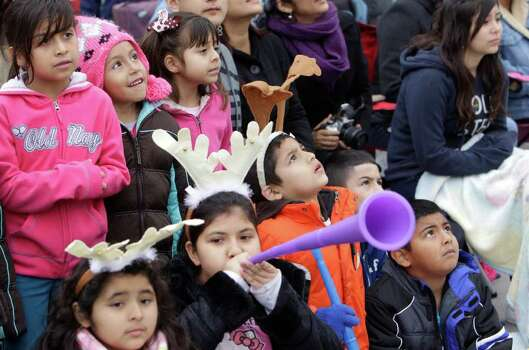 Children watch parade ballon floats during the 62nd Annual Holiday Parade on Thanksgiving Day in downtown Houston Thursday, Nov. 24, 2011. Photo: Melissa Phillip, Houston Chronicle / © 2011 Houston Chronicle