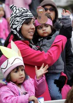Ashely Vasques, 3,  waves as her cousin, Elizabeth Fuentes helps niece, Hannah Salas, 1, wave as they watch the 62nd Annual Holiday Parade on Thanksgiving Day in downtown Houston Thursday, Nov. 24, 2011. Photo: Melissa Phillip, Houston Chronicle / © 2011 Houston Chronicle