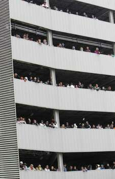 People watch from parking garage during the 62nd Annual Holiday Parade on Thanksgiving Day in downtown Houston Thursday, Nov. 24, 2011. Photo: Melissa Phillip, Houston Chronicle / © 2011 Houston Chronicle