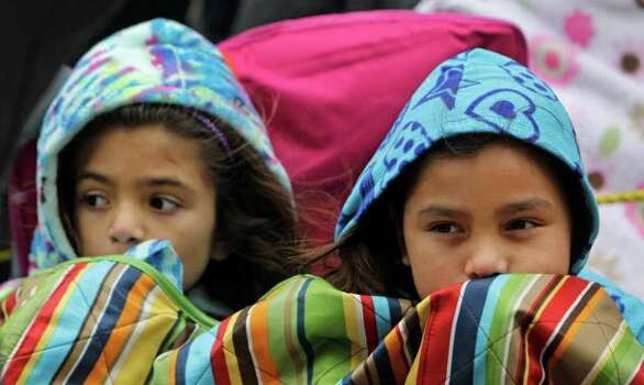 Izabel Escobar, 6, left, and her sister, Alyssa Escobar, 8, try to stay warm during the 62nd Annual Holiday Parade on Thanksgiving Day in downtown Houston Thursday, Nov. 24, 2011. Photo: Melissa Phillip, Houston Chronicle / © 2011 Houston Chronicle