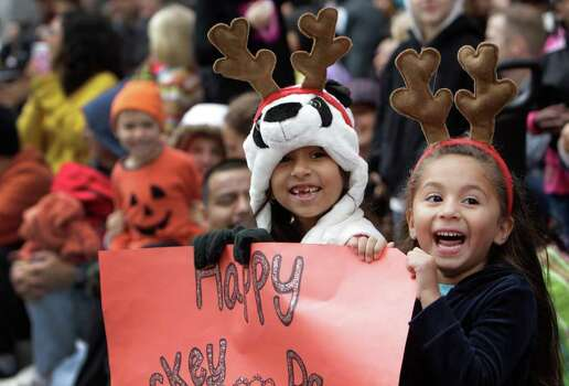 Pricilla Medina, 7, left, and her cousin Aaliyah Saiz, 4, right, wearing an assortment of head decorations watch the 62nd Annual Holiday Parade on Thanksgiving Day in downtown Houston Thursday, Nov. 24, 2011. They made a glitter sign that read Happy Turkey Day. Photo: Melissa Phillip, Houston Chronicle / © 2011 Houston Chronicle