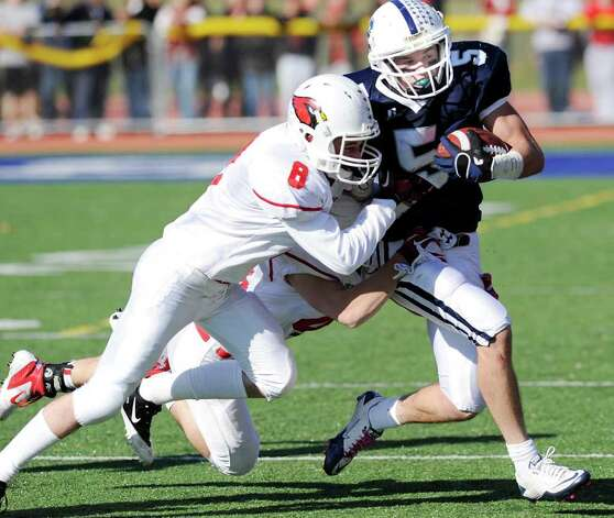 Running back Nick Kelly # 5 of Staples High School is tackled by Nick Pulitano # 8 of Greenwich High School during the FCIAC Football Championship game in which Staples High School defeated Greenwich High School 31-27 at Staples, Westport, Thursday afternoon, Nov. 24, 2011. Photo: Bob Luckey / Greenwich Time