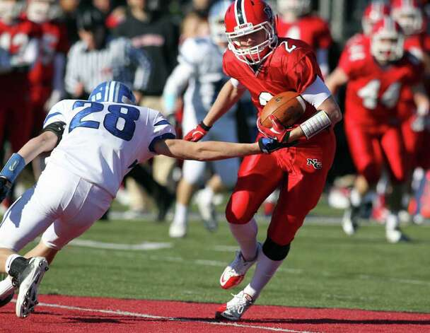 New Canaan WR Peter Kraus eludes Darien defender Ian Vanderhorn en route to a touchdown run in New Canaan's lopsided win over Darien, 42-21.   © J. Gregory Raymond Photo: J. Gregory Raymond / © J. Gregory Raymond for The Advocate