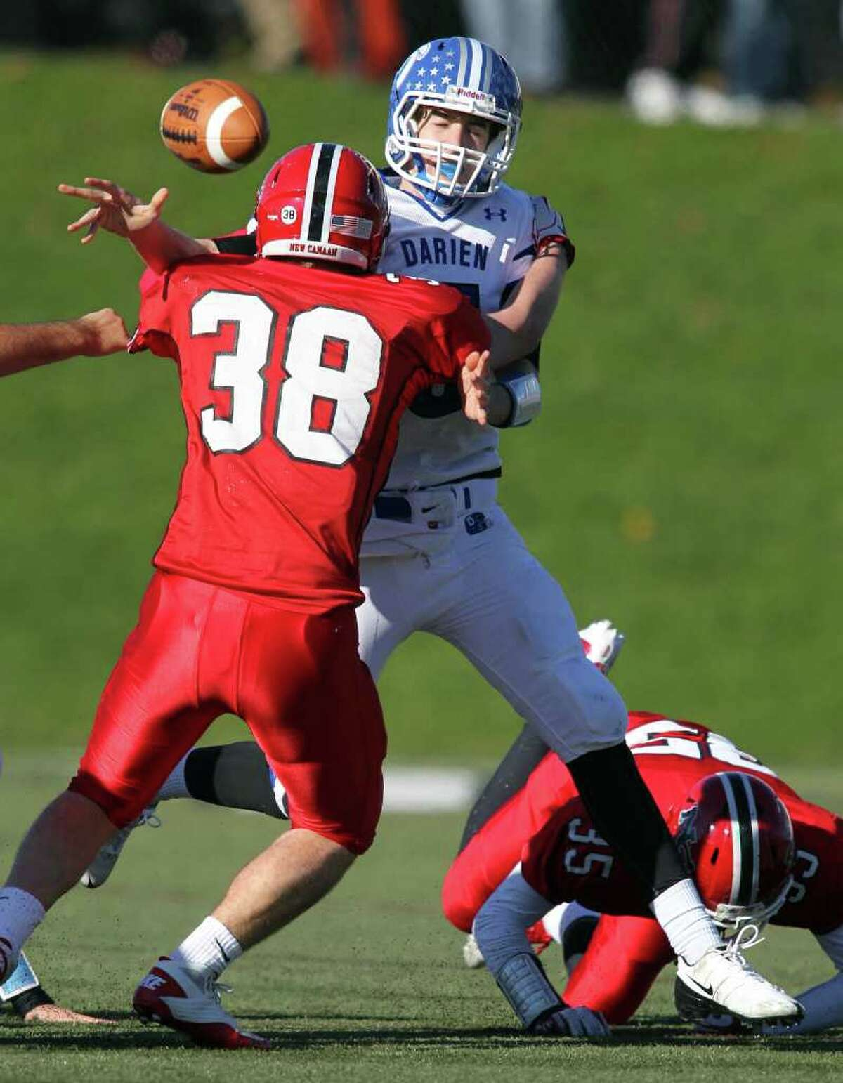 Hunter Budd of New Canaan applies defensive pressure against Darien QB Henry Baldwin forcing Baldwin to throw a harried and incomplete pass in third quarter Thanksgiving Day action. New Canaan manhandled Darien, 42-21.