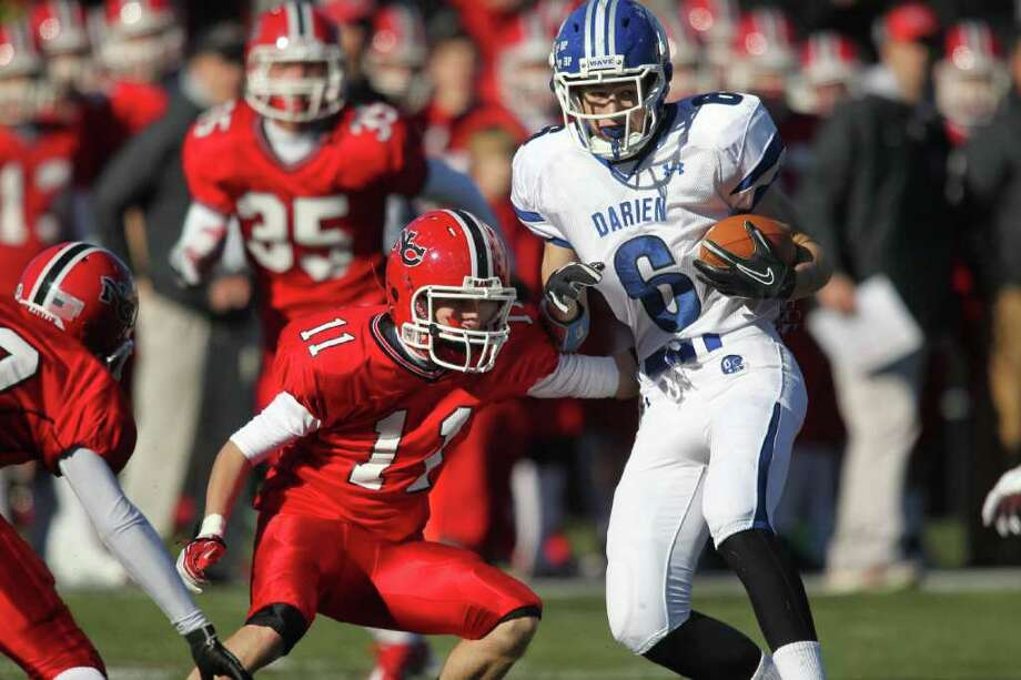 Darien WR Harlan Smith looks to elude New Canaan defender Patrick Burke following a second half reception by Smith. New Canaan clobbered Darien, 42-21 in the annual Thanksgiving Day event.  © J. Gregory Raymond Photo: J. Gregory Raymond / © J. Gregory Raymond for The Advocate