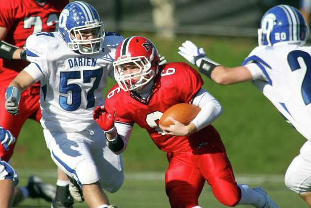 New Canaan sophomore Ted Bossidy spits Darien defenders Tyler Maul and Michael Stovall en route to a fourth quarter gain during gridiron action between the two schools. New Canaan clobbered Darien, 42-21.  © J. Gregory Raymond Photo: J. Gregory Raymond / © J. Gregory Raymond for The Advocate