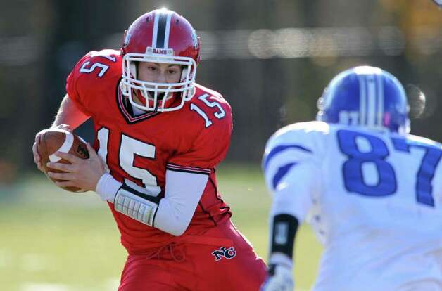 Matt Milano of New Canaan attempts to elude Darien defender Jackson Whiting during third quarter action between the two schools. New Canaan won the game easily, 42-21.  © J. Gregory Raymond Photo: J. Gregory Raymond / © J. Gregory Raymond for The Advocate