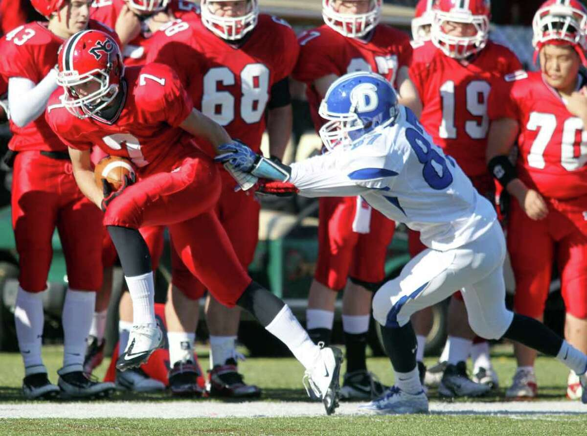 New Canaan WR Grady Lynch runs upfield for additional yards while Darien defender Jackson Whiting attempts to tackle him. Led by QB Matt Milano, New Canaan won the game easily, 42-21.