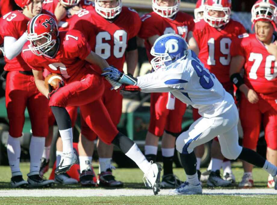 New Canaan WR Grady Lynch runs upfield for additional yards while Darien defender Jackson Whiting attempts to tackle him. Led by QB Matt Milano, New Canaan won the game easily, 42-21. Photo: J. Gregory Raymond / © J. Gregory Raymond for The Advocate