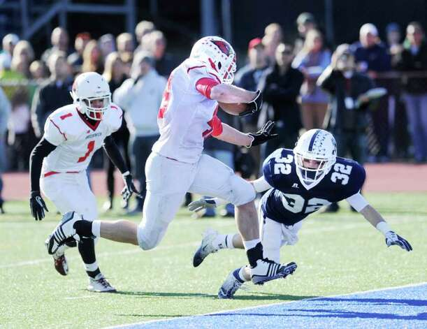 Greenwich High School running back Shane Nastahowski, center, evades the tackle of Austin Lazar # 32 of Staples High School to score a touchdown during the FCIAC Football Championship game in which Staples High School defeated Greenwich High School 31-27 at Staples, Westport, Thursday afternoon, Nov. 24, 2011. In the background is Vincent Ferraro # 1 of Greenwich High School. Photo: Bob Luckey / Greenwich Time