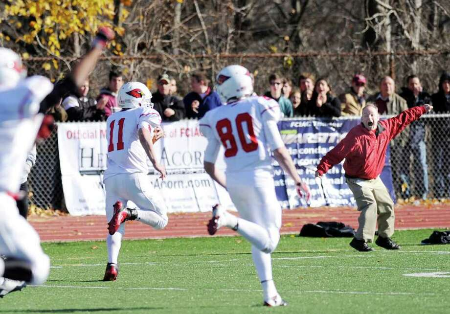 With Greenwich High School's Brian Kennedy, right, cheering him on from the sidelines, Alex McMurray # 11 goes 68 yards for a touchdown on a reception during the FCIAC Football Championship game in which Staples High School defeated Greenwich High School 31-27 at Staples, Westport, Thursday afternoon, Nov. 24, 2011.  In foreground is Joe Kelly # 80 of GHS. Photo: Bob Luckey / Greenwich Time