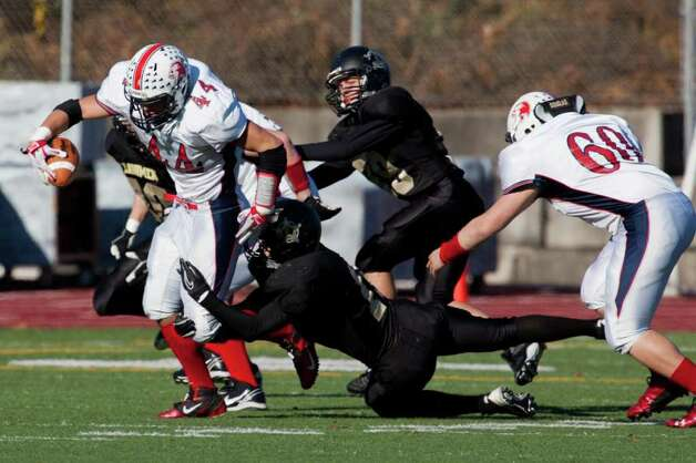 Foran High School's # 44 Dave Yerxa gains yardage as Jonathan Law High School #16 Matt Ferraiolo completes a tackle during Thanksgiving Day Match at Jonathan Law High in Milford. Foran would win 48-13. Photo: Mike Ross / Connecticut Post freelance